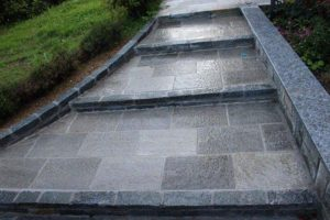 Scalinata esterna rivestita con pietra di Luserna a piastrelle e liste da muto per cordoli alzate